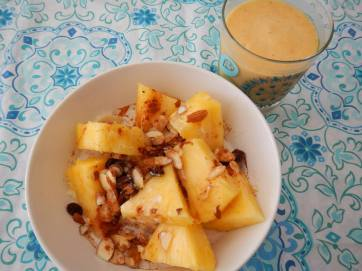 quinoa cinnamon almond breakfast bowl with tropical fruit medley and coconut milk and banana pineapple mango smoothie